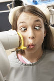Teenage girl (14-16) having x-ray taken in dental surgery, pulling funny face, close-up, front view Royalty Free Stock Photography