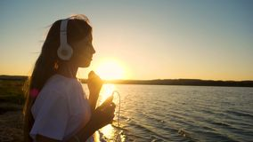 Girl teenager headphones and with phone at sunset. Slow motion. Teenage girl in headphones dancing at sunset evening listening to music on phone. Slow motion stock video