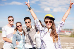 Teenage girl with headphones and friends outside Royalty Free Stock Photography