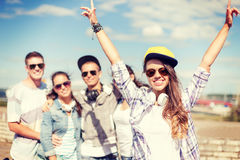 Teenage girl with headphones and friends outside Stock Photo