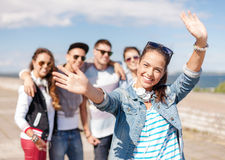 Teenage girl with headphones and friends outside Royalty Free Stock Photos