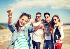 Teenage girl with headphones and friends outside Stock Images