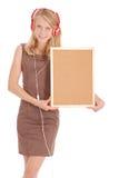 Teenage girl in headphones, holding cork board Royalty Free Stock Images