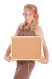 Teenage girl in headphones, holding cork board Royalty Free Stock Image