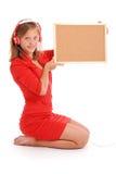 Teenage girl in headphones, holding cork board Stock Photography