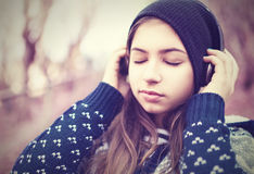 Teenage girl in headphones listens to music with closed eyes. Outdoors Royalty Free Stock Photo