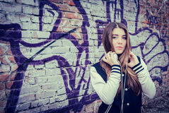 Teenage girl  with headphones near graffiti wall Stock Photography