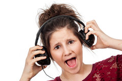 Teenage Girl with Headphones. Teenage girl shocked at lound music with headphones in studio on white background Royalty Free Stock Photos