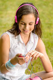 Teenage girl with headphones sitting on grass Royalty Free Stock Photography