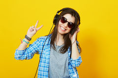 Teenage girl with headphones smiling showing peace gesture Royalty Free Stock Images