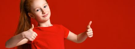 Teenage girl with healthy freckled skin, wearing a red t-shirt, looking at the camera shows big thumbs up, happy facial expression royalty free stock image