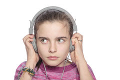 Teenage girl hears something scary on headphones. Isolated on white Royalty Free Stock Image