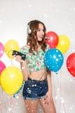 Teenage girl with helium balloons over gray background stock photo