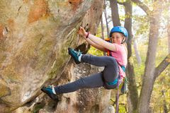 Teenage girl in helmet climbing on the rock route stock photo
