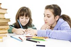 Teenage girl helping his sister with her homework. Studi shoot royalty free stock image