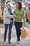 Teenage Girl Helping Senior Woman To Carry Shopping Stock Photography