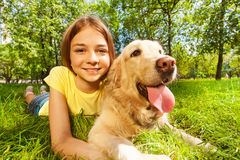 Teenage girl with her dog laying in park. Funny wide angle portrait of happy smiling teenage girl and her happy golden retriever dog pet laying in the grass of stock photography
