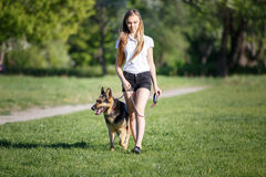 Teenage girl with her dog walking in park. Teenage girl in white shirt with her german shepherd dog walking in the park Royalty Free Stock Image