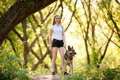 Teenage girl with her dog walking in park. Teenage girl in white shirt with her german shepherd dog standing on pathway in the forest Royalty Free Stock Photos