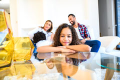 Teenage girl with her family. Portrait of a young teenage african girl leaning on a coffee table while her family siting on a coach behind herr royalty free stock photos