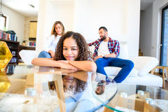 Teenage girl with her family. Portrait of a young teenage african girl leaning on a coffee table while her family siting on a coach behind herr royalty free stock image