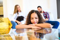 Teenage girl with her family. Portrait of a young teenage african girl leaning on a coffee table while her family siting on a coach behind herr royalty free stock photography