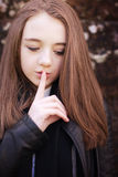 Teenage girl with her finger to her lips for silence Royalty Free Stock Photos