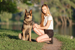 Teenage girl with her german shepherd in park. Teenage girl in white shirt with her german shepherd sitting on pathway in the park Stock Photography