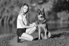 Teenage girl with her german shepherd in park. Teenage girl in white shirt with her german shepherd sitting on pathway in the park Stock Images
