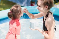 Teenage girl with her little sister spending time together in the swimming pool in a garden enjoy eating ice cream. On a summer sunny day. Family quality time Royalty Free Stock Photos