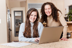 Teenage girl with her mother. A happy teenage girl and her mother using laptop at home royalty free stock photos