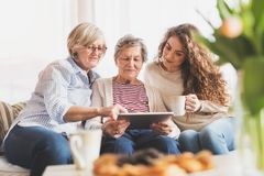 A teenage girl, mother and grandmother with tablet at home. A teenage girl, her mother and grandmother with tablet at home. Family and generations concept stock photos