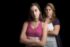 Teenage girl and her mother sad and angry. At each other isolated on black stock photography