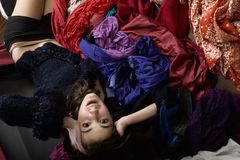 Teenage girl in her room. A young girl lying on the floor in panic next to a mess of clothes inside her room Royalty Free Stock Image
