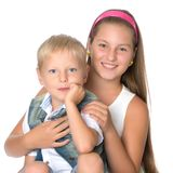 A teenage girl with her younger brother. Studio photo session. The concept of family happiness.Isolated on white background Stock Photography