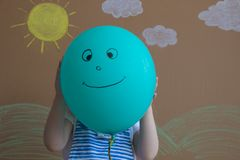 Teenage girl hiding their faces behind smiling balloons. Background of painted sun and white clouds royalty free stock photos
