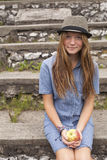 Teenage girl hipster in a hat and an apple in his hands Royalty Free Stock Photography
