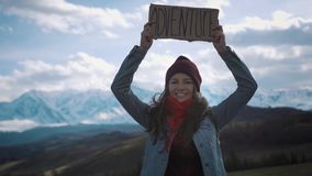 Teenage Girl Holding An Adventure Sign On A Mountain Road, Smiles And Laughs.  stock footage