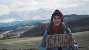 Teenage Girl Holding An Adventure Sign On A Mountain Road, Smiles And Laughs stock video