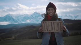 Teenage Girl Holding An Adventure Sign On A Mountain Road, Smiles And Laughs.  stock video