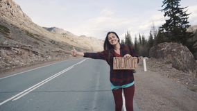 Teenage Girl Holding An Adventure Sign On A Mountain Road, Smiles And Laughs. Hitchhiking in search of adventure. stock footage