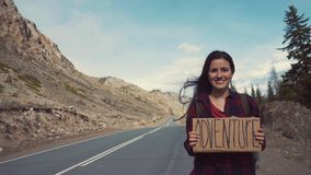Teenage Girl Holding An Adventure Sign On A Mountain Road, Smiles And Laughs. Hitchhiking in search of adventure. stock video