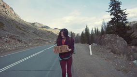 Teenage Girl Holding An Adventure Sign On A Mountain Road, Smiles And Laughs. Hitchhiking in search of adventure. Teenage Girl Holding An Adventure Sign On A stock video footage