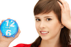 Teenage girl holding alarm clock Royalty Free Stock Images