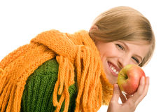 Teenage girl holding apple laughing. Pretty autumnal teenage girl holding apple laughing isolated on white background Royalty Free Stock Photography