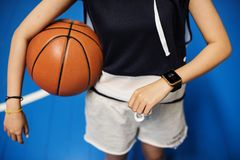 Teenage girl holding a basketball on the court Stock Images