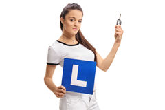 Teenage girl holding a car key and an L-sign Royalty Free Stock Image