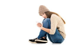 Teenage girl holding cell phone looking scared. Difficult life situation, relationship problems, rebellious age. Teenage girl holding smartphone, waiting for royalty free stock photo
