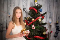 Teenage girl holding Christmas present in front of New Year tree Royalty Free Stock Photo