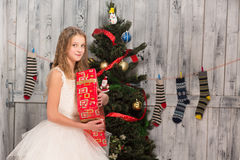 Teenage girl holding Christmas present in front of New Year tree Stock Image